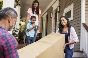Family Carrying Big Box Purchase Into House