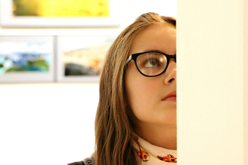 Girl with glasses looking at painting in museum