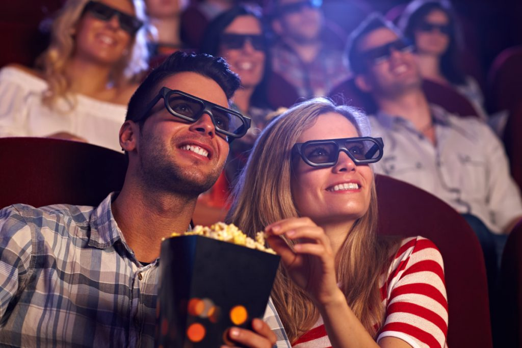 Couple watching movie at theater with glasses and popcorn