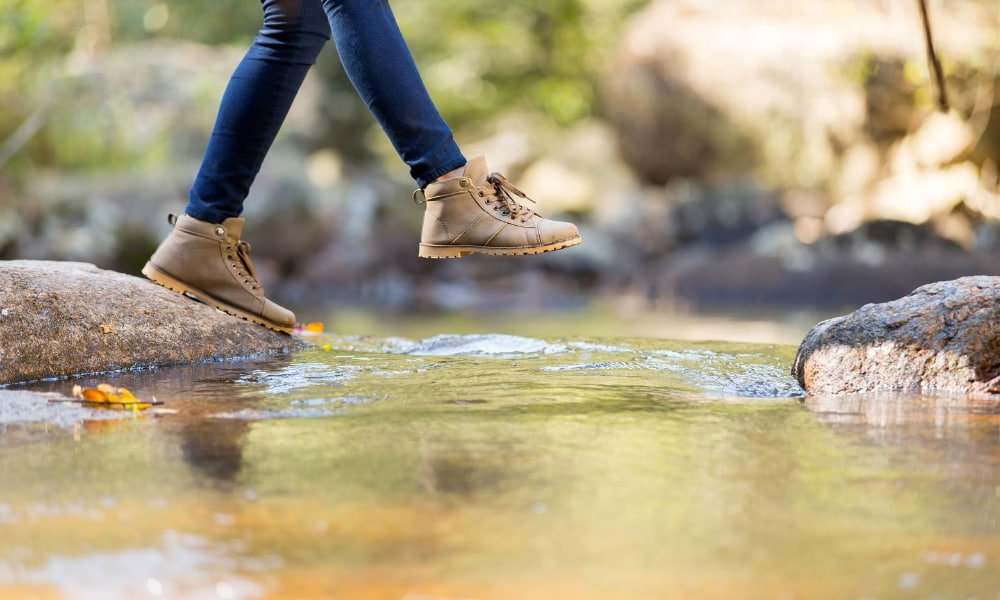 person hiking across river