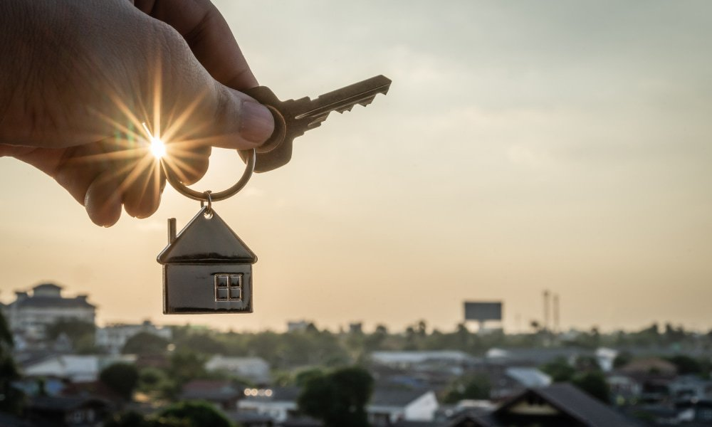 A person holding keys after buying a rental property