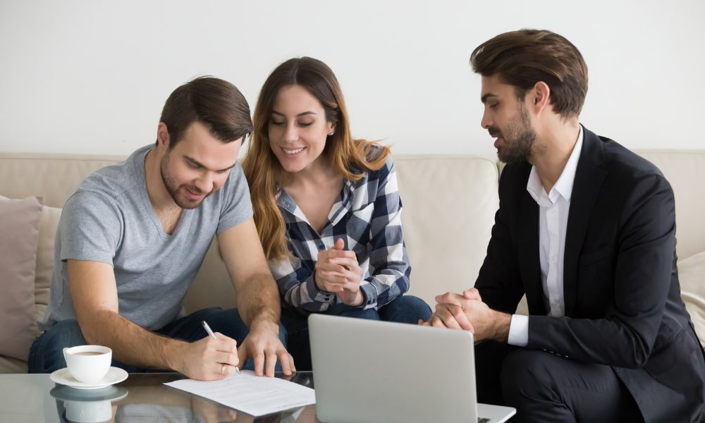 Couple completing rental application process with landlord