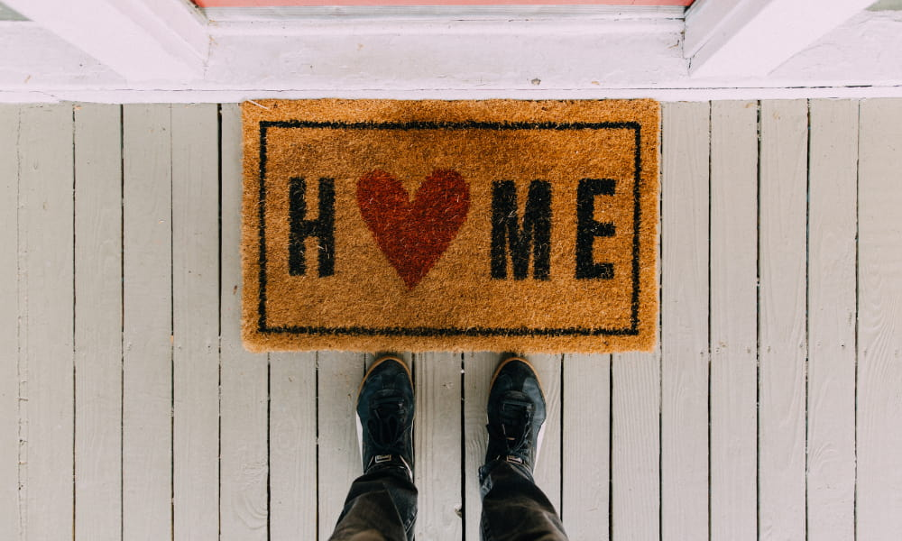 Welcome mat in front of house that says home