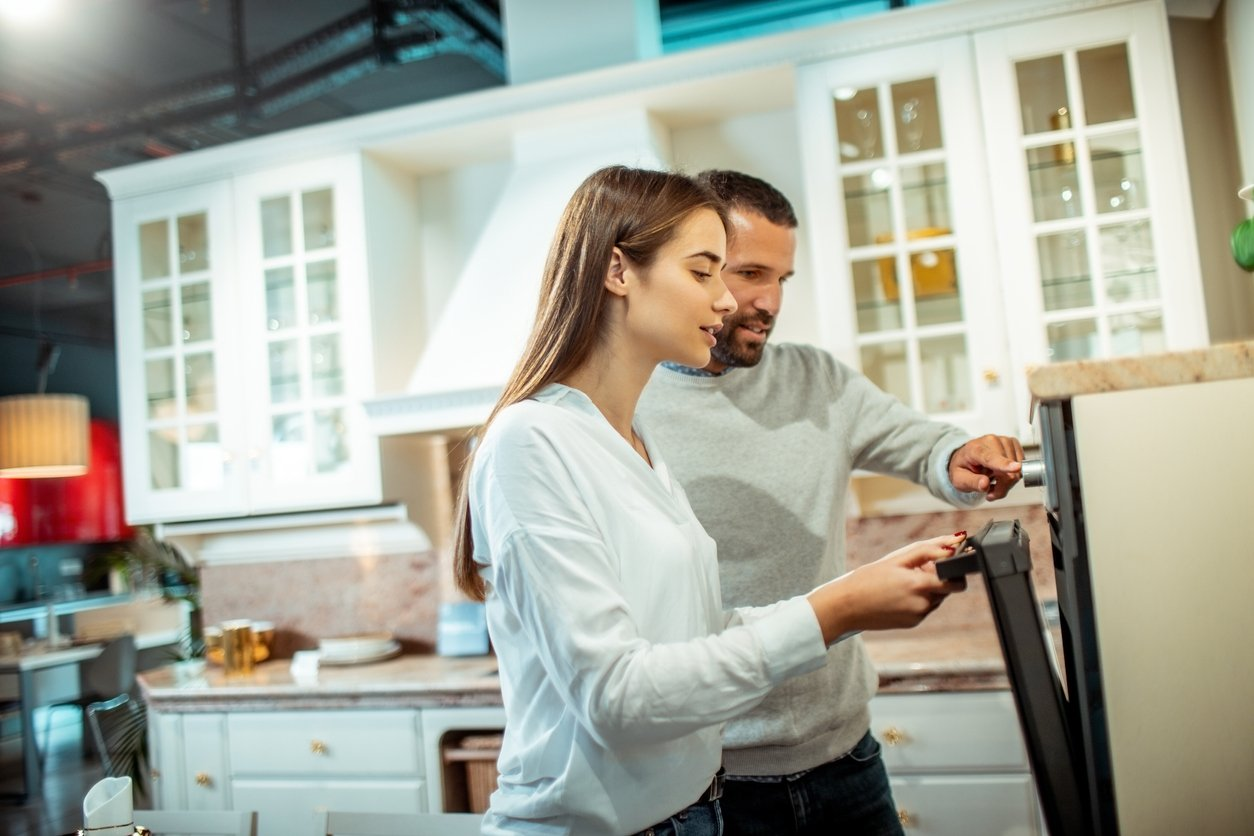 young couple looking at new appliances for rental property