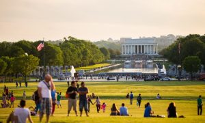 Tourists enjoy the lawn during a sunny day in front of the Lincoln Memorial on the National Mall.