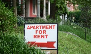 Apartment for rent sign in the front yard of a residential building, illustrating the occasional need for landlord rental concessions.