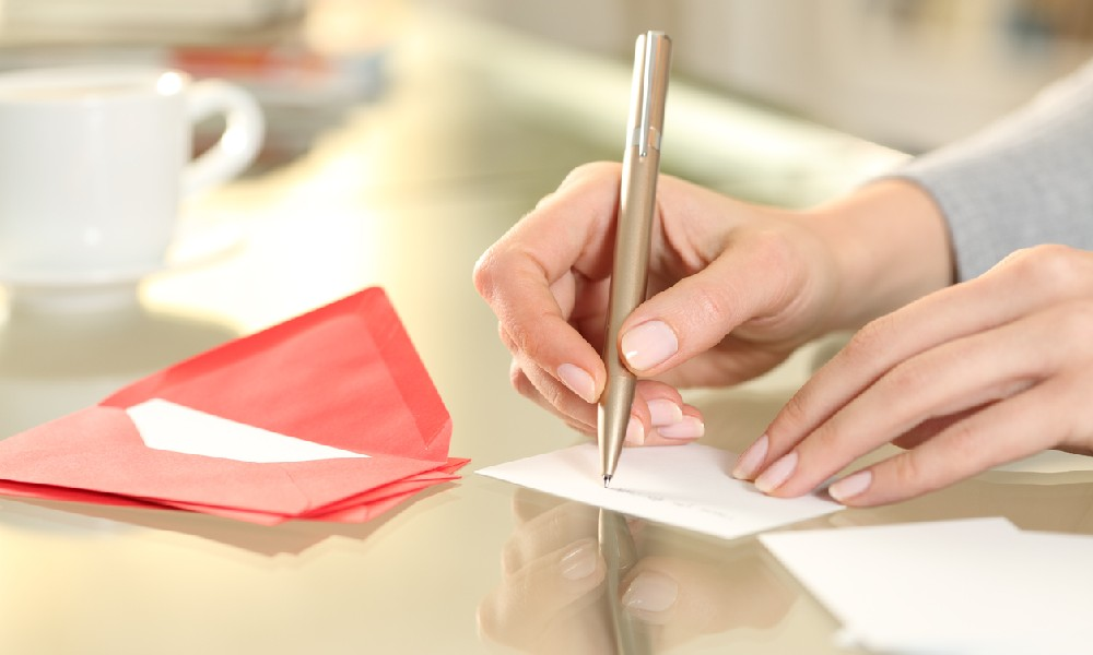 A woman's hands are writing a tenant welcome letter before new renters move into her home.