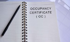 White notebook paper with black ink pen and words occupancy certificate (OC) in bold typeface, signifying a certificate of occupancy in D.C.