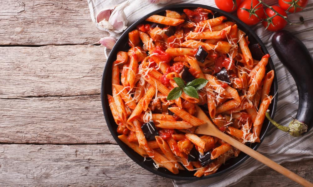 a bowl of italian penne pasta and tomato sauce