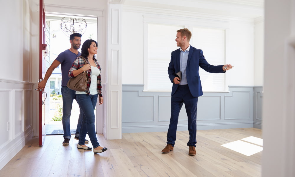 A representative of a foreign service officer property management firm shows a home to potential tenants.