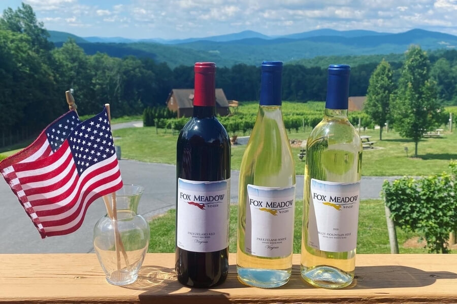 small american flag in a cup, one red wine bottle and two white wine bottles on a balcony with the view of the Fox Meadow winery