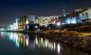 Skyline view shows homes and restaurants in Potomac along the riverfront under the twinkling night sky.